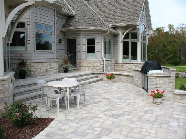 Green Bay Outdoor Living Space with a Grill Area and Granite Counter next to a Paver Patio