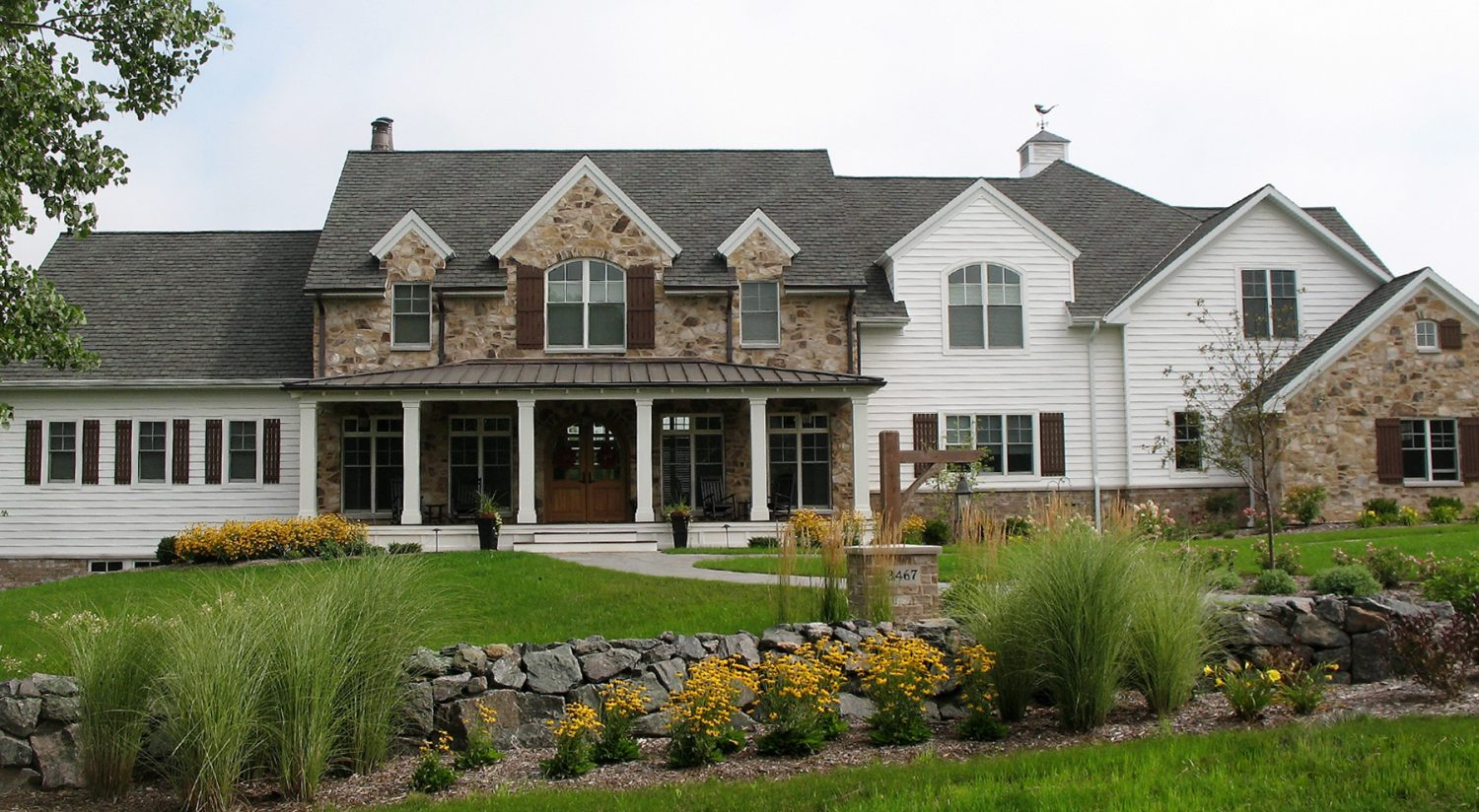 A large house with a manicured front lawn, featuring a retaining wall with flowers and shrubs in a mulch bed. It is a good example of our landscape design work.