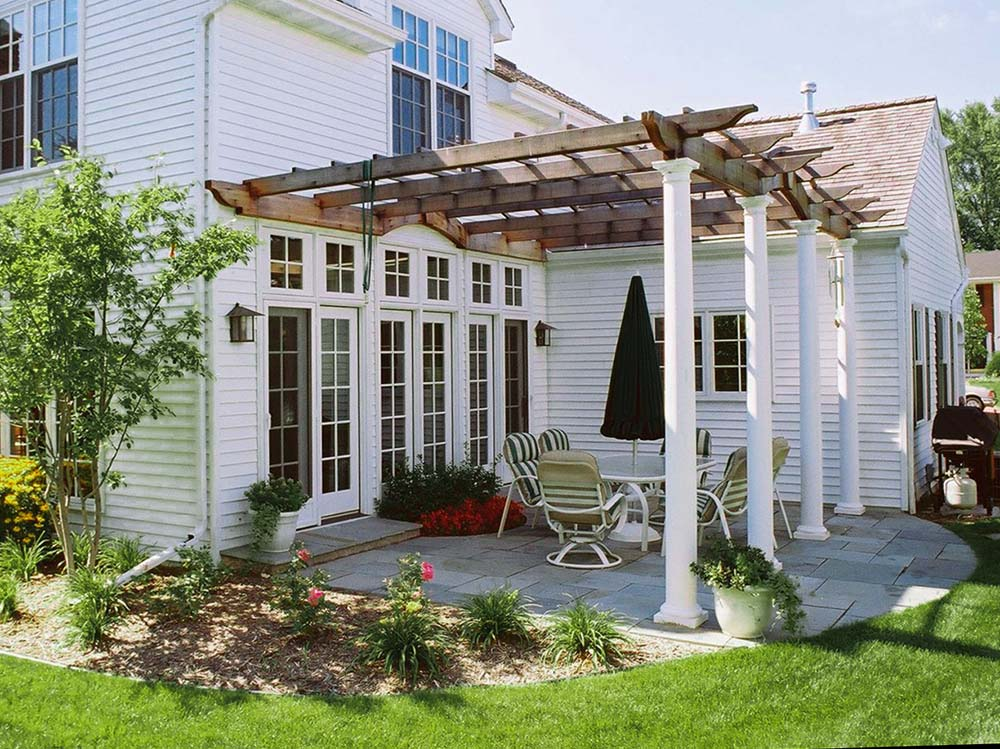 A pergola covering a stone patio attached to the back of a white house.