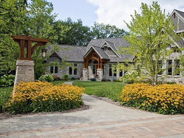 Arts & Crafts historic home surrounded by beautiful landscaping.