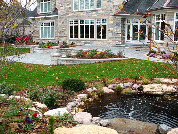 Large stone estate with patio, landscaping, and pond.