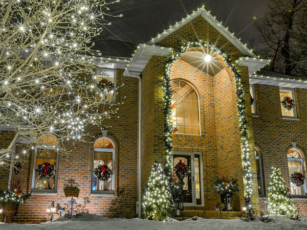 Large 2 story brick house with decorative Christmas trees and wreaths lit up at night.