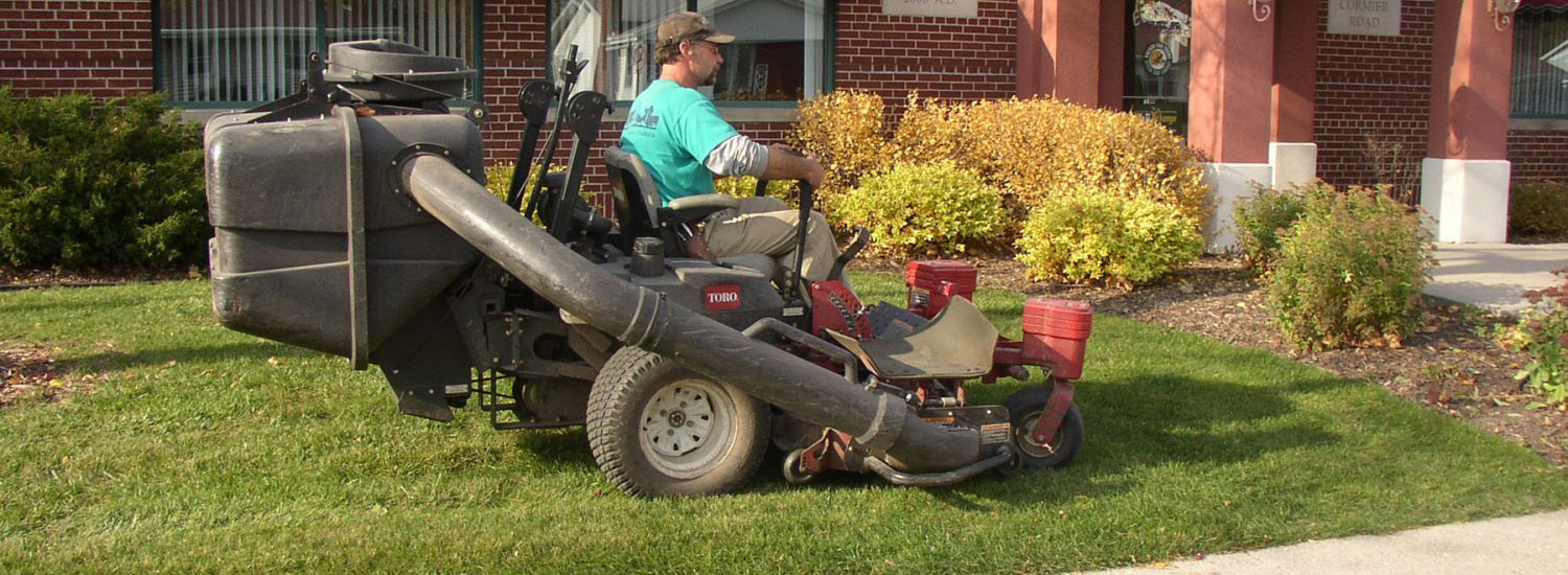 A Landscape worker on a riding lawn mower mowing a residential property.