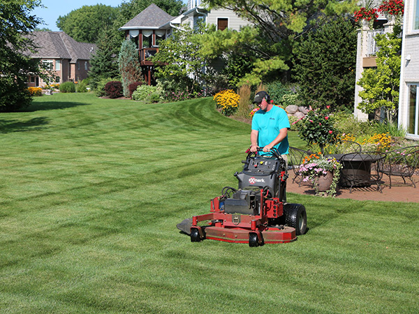 A landscape worker on a riding lawn mower, mowing a commercial property.