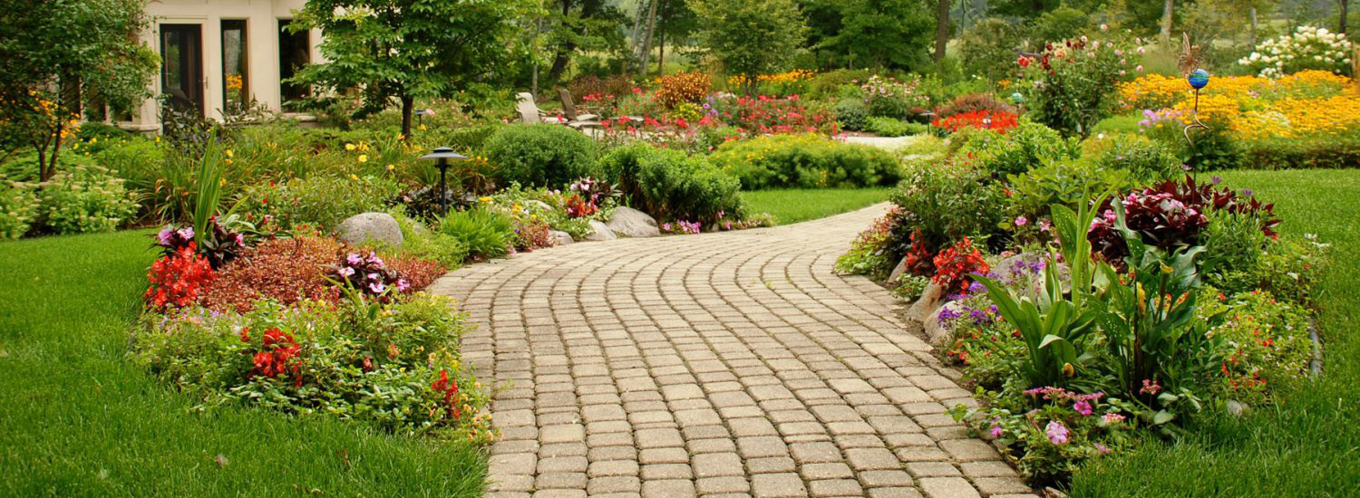 A paver walkway lined with colorful plantings.