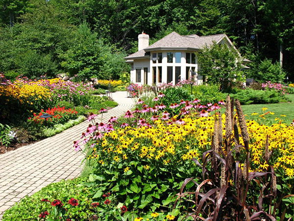 Home in wilderness with large paver walkway and many landscaped plants and flowers.