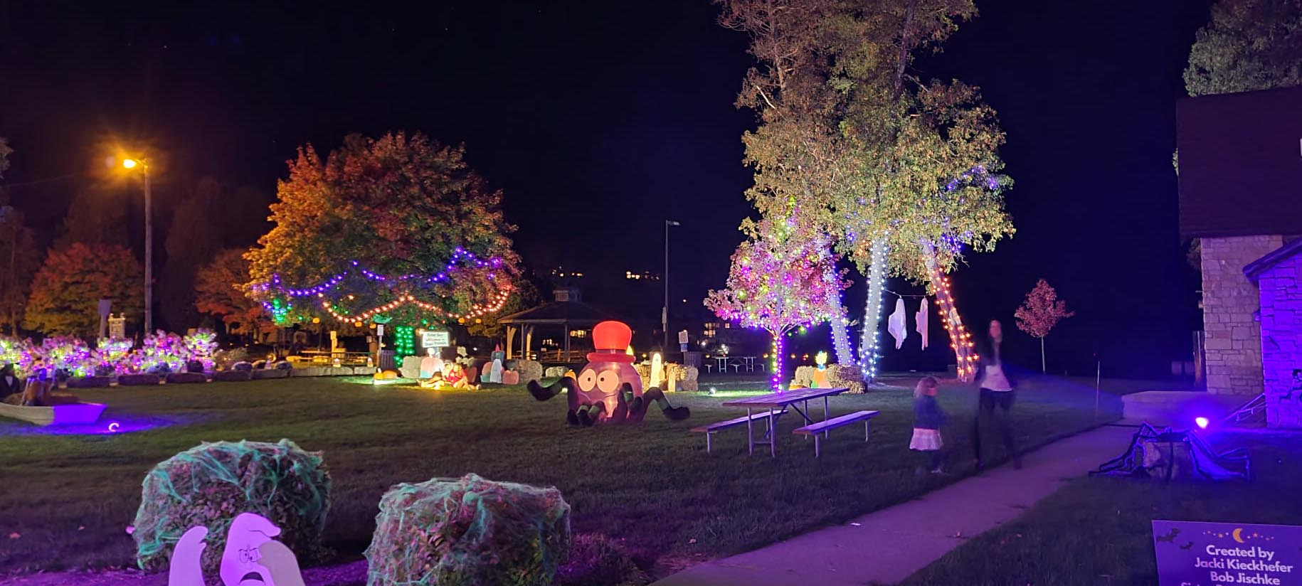 Outdoor park decorated with lights and Halloween decorations.