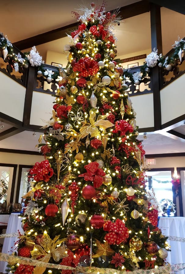 Large Christmas tree covered in red and gold decorations.